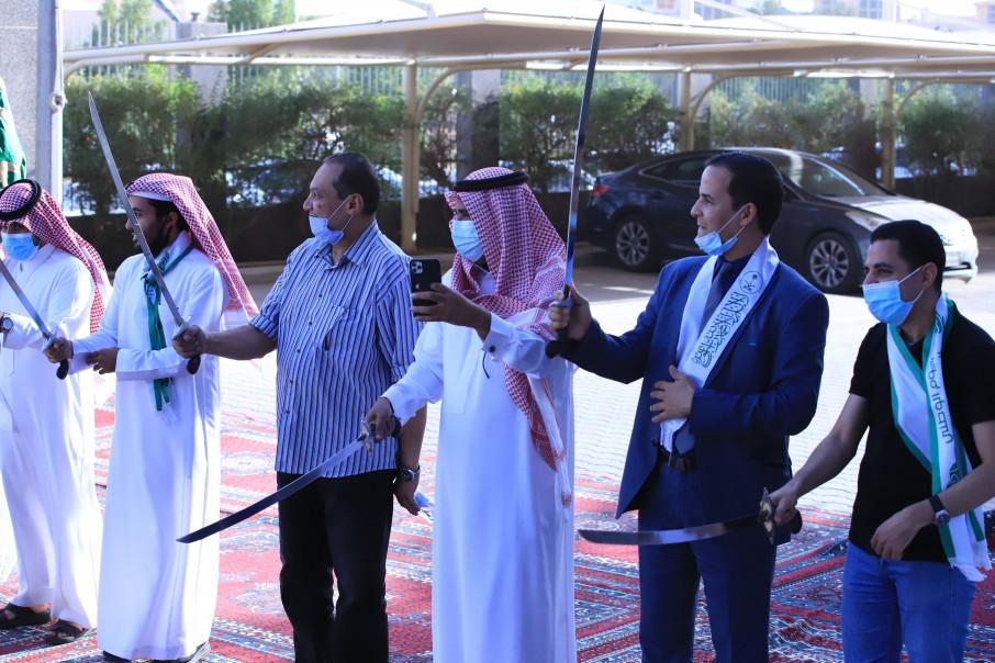 عميد كلية الدراسات العليا وأعضاء هيئة التدريس والطلاب يشاركون في أداء العرضة السعودية